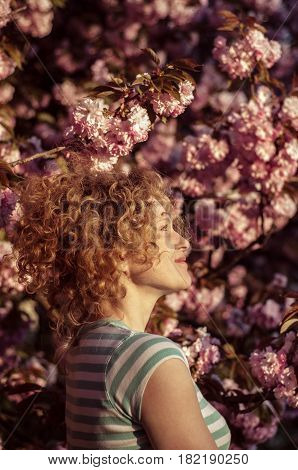 The girl admires the flowering cherry blossom