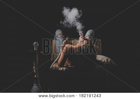 traditional arabic kalian pretty woman with sexy back and body in jeans sitting on eastern chair with shisha bong naked girl smoking hookah on black background