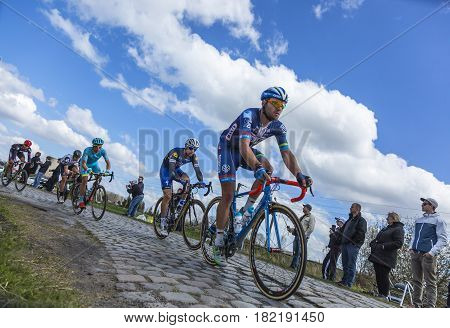 Hornaing France - April 102016: Group of three cyclists riding in the peloton on a paved road in Hornaing France during Paris Roubaix on 10 April 2016.