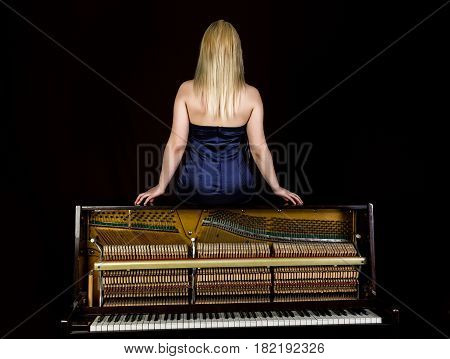 back view of fashion young woman sitting on old retro wooden piano with keyboard and posing.