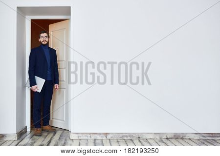 Man in glasses standing in doorway and looking at camera coming into office for job interview