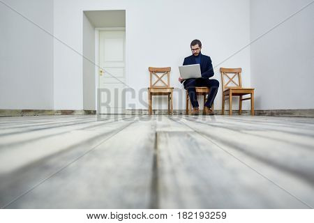 Low angle portrait of bearded man using laptop while sitting on chair in waiting room by office door
