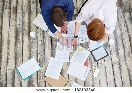 Above view of two business people sorting documents laying papers out of floor in office and discussing work