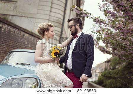 Newlywed couple standing in the street next to an old retro car hugging and embarking on a honeymoon