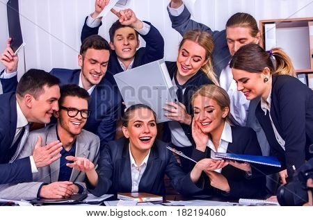 Business people office life of team people are happy with hand up sitting table and working papers . Cabinets with folders and jalousie background.