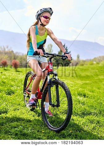 Woman traveling bicycle in summer park. Womens road bike for running on green grass in summer morning. Cycling trip is good for health.