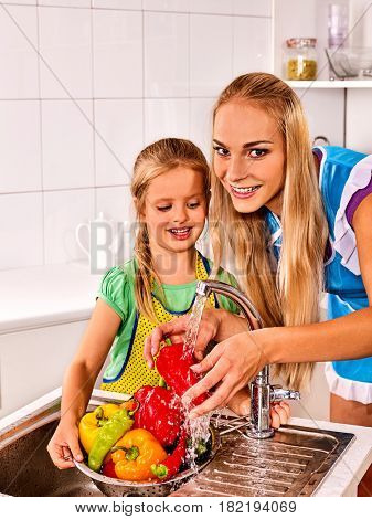 Fruit and vegetable wash of woman with daughter on kitchen home. Girl washing vegetables under pouring water tap in colander sink indoor.