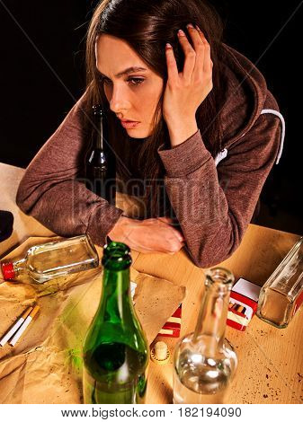 Woman alcoholism is social problem. Female drinking is cause of nervous stress . She with green alcohol bottle in bad mood . Drunken woman sadly look at camera. Top view.