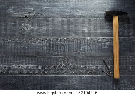 hammer tool and nail at wooden background