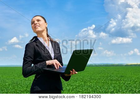 Business concept - woman in green grass field outdoor work on laptop. Young girl dressed in black suit. Beautiful spring landscape with cloudy sky, bright sunny day