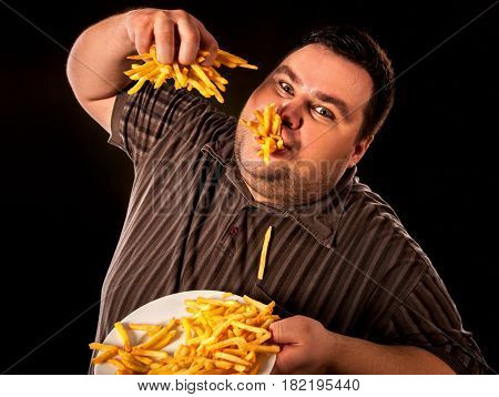 Diet failure of fat man eating fast food . Overweight person who spoiled healthy food by eating french fries. Junk meal leads to obesity.