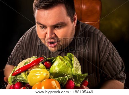 Diet fat man eating healthy food . Healthy breakfast with vegetables cauliflower and sweet pepper with radish for overweight person. Male trying to lose weight. Concept on black background.
