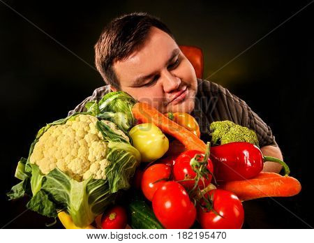 Diet fat man eating healthy food with vegetables cauliflower and sweet pepper with radish , tomatoes for overweight person. Male trying to lose weight and rejoices at advent of summer and vitamins