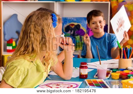 Small students girl and boy painting in art school class. Child drawing by paints on table. Male kid shows his drawing in kindergarten. Craft drawing education develops creative abilities of children.