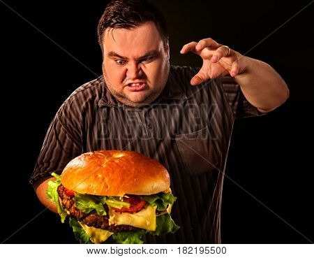 Diet failure of fat man eating fast food hamberger. Aggressive overweight person who spoiled healthy food by eating huge hamburger. Junk meal leads to obesity.