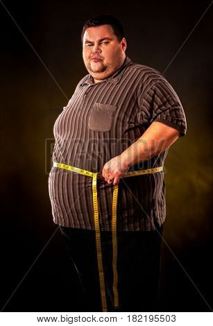 Man belly fat with tape measure weight loss around body on black background.