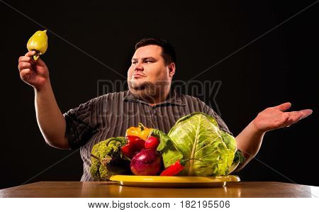 Diet fat man eating healthy food . Health breakfast with vegetables cauliflower and sweet pepper with radish for overweight person. Male trying to lose weight and rejoices in healthy eating.