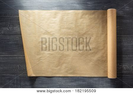 scroll of brown paper at wooden background texture
