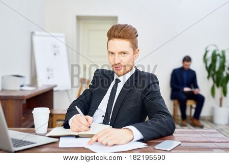 Portrait of handsome young businessman looking at camera with smirk while writing in planner at desk in office, employee in background
