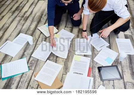 Assorted documents and contracts laid out on wooden office floor with  two business  people busy working and sorting it