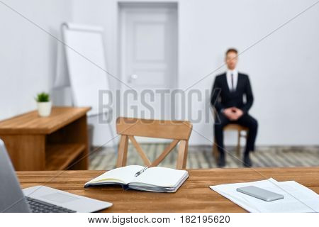 Empty workplace: old school wooden desk with laptop in spacious light office, business person in background