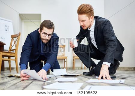 Portrait of two adult men sorting documents on floor in office while working and making plans