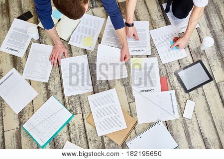 Above view of assorted documents and contracts laid out on wooden office floor with hands of two unrecognizable  business people working