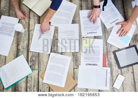 Top view of assorted documents and contracts laid out on wooden office floor with hands of two unrecognizable  people working