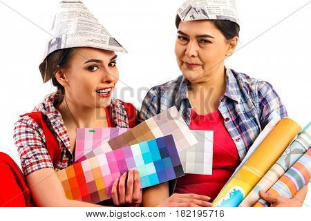 Repair home women holding color guide for wallpaper. Elderly mother in newspaper hat and daughter sitting on floor and renovation apartment on isolated.