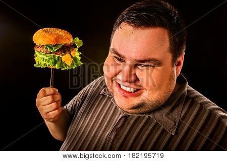 Diet failure of fat man eating fast food hamberger. Happy smile overweight person who spoiled healthy food by eating huge hamburger on fork. Junk meal leads to obesity.