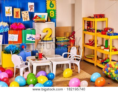 Kindergarten interior decoration child picture wall. Preschool class waiting kids. Colour balloons on floor in creative room. Playroom with white table. Art room for education children's creativity.