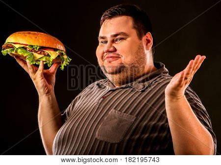 Man eating fast food hamberger. Fat person cooked terrific cheeseburger and admires him, intending to eat it. Junk meal leads to obesity. Person regularly overeats concept .