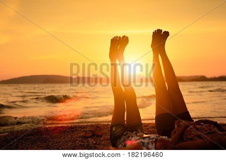 Mother and her daughter lift up they feet to sky on the beach