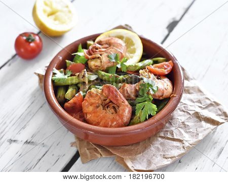 Jumbo Shrimps or prawns and green asparagus on a white wood table. Delicious gourmet dish. Spanish tapas.