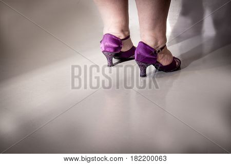 Woman dancing with lilac salsa sandals. Night club.
