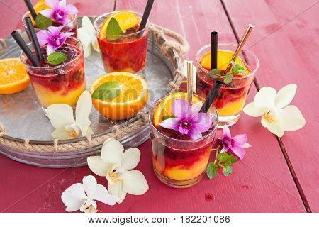 Colorful cocktail with fresh fruits and colorful orchids