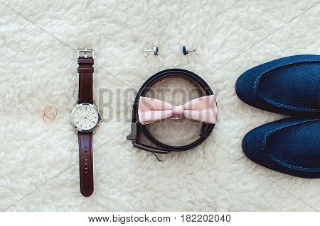 Close up of modern man accessories. Biege bowtie, leather shoes, belt, watch, cufflinks and wedding rings. formal style of wearing. look from above