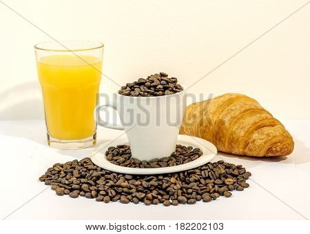 Cup of coffee filed with coffee beans with orange juice and croissants on white background
