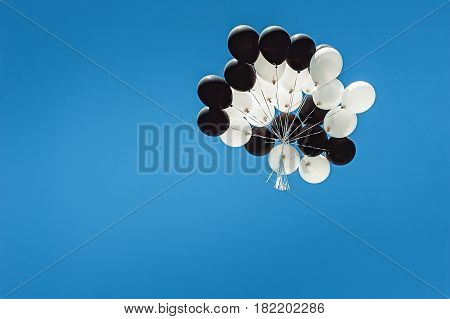 set of black and white balloons high in the sky. cloudless blue sky.