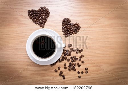 Hot cup of espresso and heart shape made from coffee beans on wooden surface. White mug of hot drink.