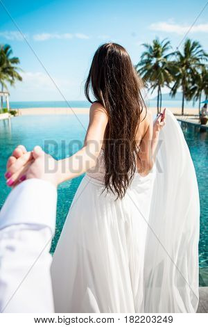 Sexy bride in white dress holding groom in luxury resort. Romantic woman leading man to swimming pool. Fiance follow fiancee. Tropical country. Caucasian model with long brown hair.