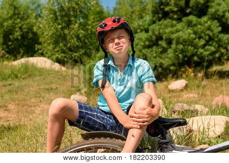 Teenager has a leg injury, bicycle lies nearby