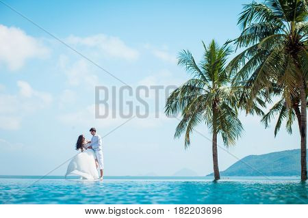 Newly married couple after wedding in luxury resort. Romantic bride and groom relaxing near swimming pool and sea. Honeymoon. Tropical country.
