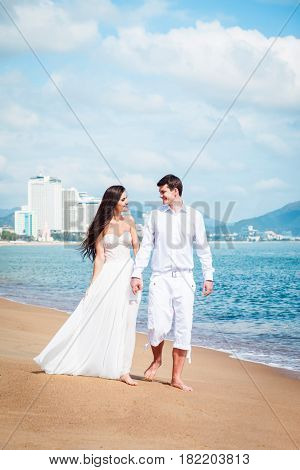Newly married couple after wedding in luxury resort. Romantic bride and groom relaxing near sea. Honeymoon. Tropical country.