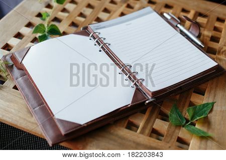 Open notepad with a ballpoint pen on the summer table