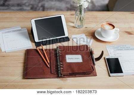Notepad For Planning, Two Pencils, A Pen, A Smartphone, A Tablet And A Cup Of Coffee On A Wooden Tab