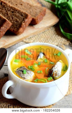 Diet, simple and tasty fish soup. Home fish soup with potatoes, carrots and green onions in a bowl. Rye bread pieces, fresh green onion on vintage wooden table. Closeup. Vertical photo