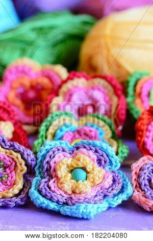 Crochet multi-colored flowers set. Crochet flower motifs and patterns. Interesting hobby for women and children. Closeup. Vertical photo