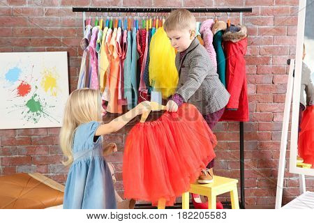 Cute little children choosing clothes in dressing room