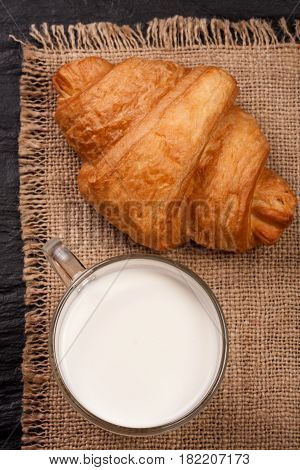 glass of milk with croissant on sackcloth . Top view.